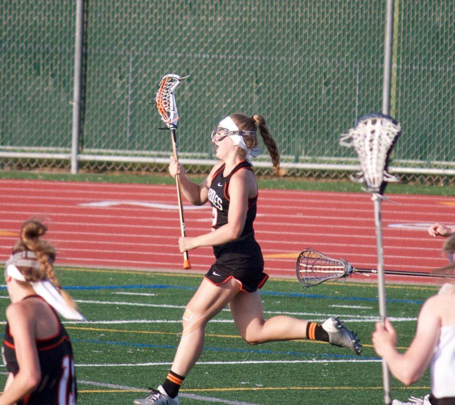 Junior+Annie+Van-Pilsum+Johnson+runs+on+the+attack+in+the+offensive+zone+during+a+lacrosse+game.+Van-Pilsum+Johnson+plays+lacrosse+and+lifts+weights+in+her+time+off+nordic+in+order+to+stay+in+shape.