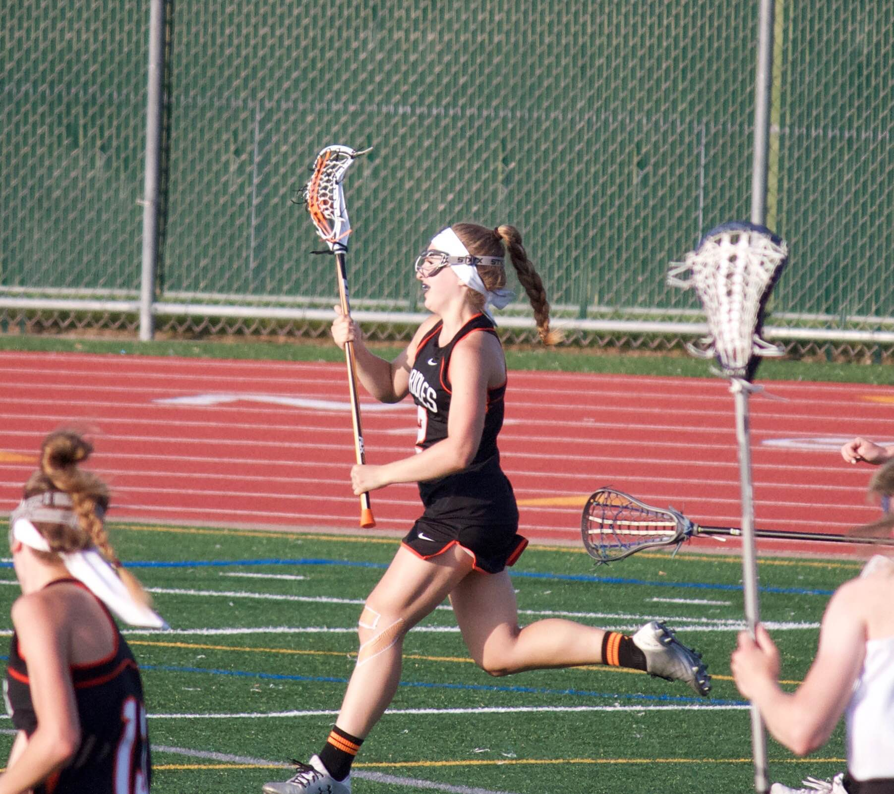 Junior Annie Van-Pilsum Johnson runs on the attack in the offensive zone during a lacrosse game. Van-Pilsum Johnson plays lacrosse and lifts weights in her time off nordic in order to stay in shape.