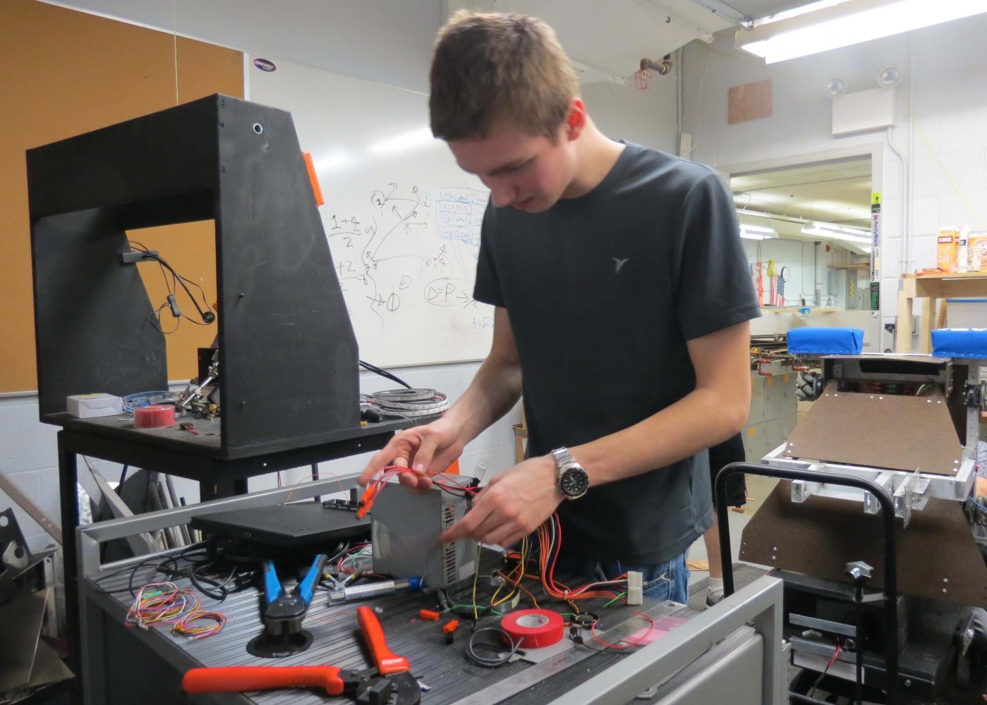 Junior captain, George O'Hare, wires a control module in preparation for Sections during a work day Mar. 24.