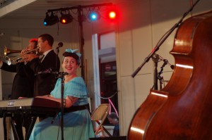 Davina Sower of Davina and the Vagabonds looks back at upright bassist Michael Carvale. In the foreground Dan Eikmeier, trumpet and Ben Link, trombone provide a jazzy overtone for Sower's vocals.