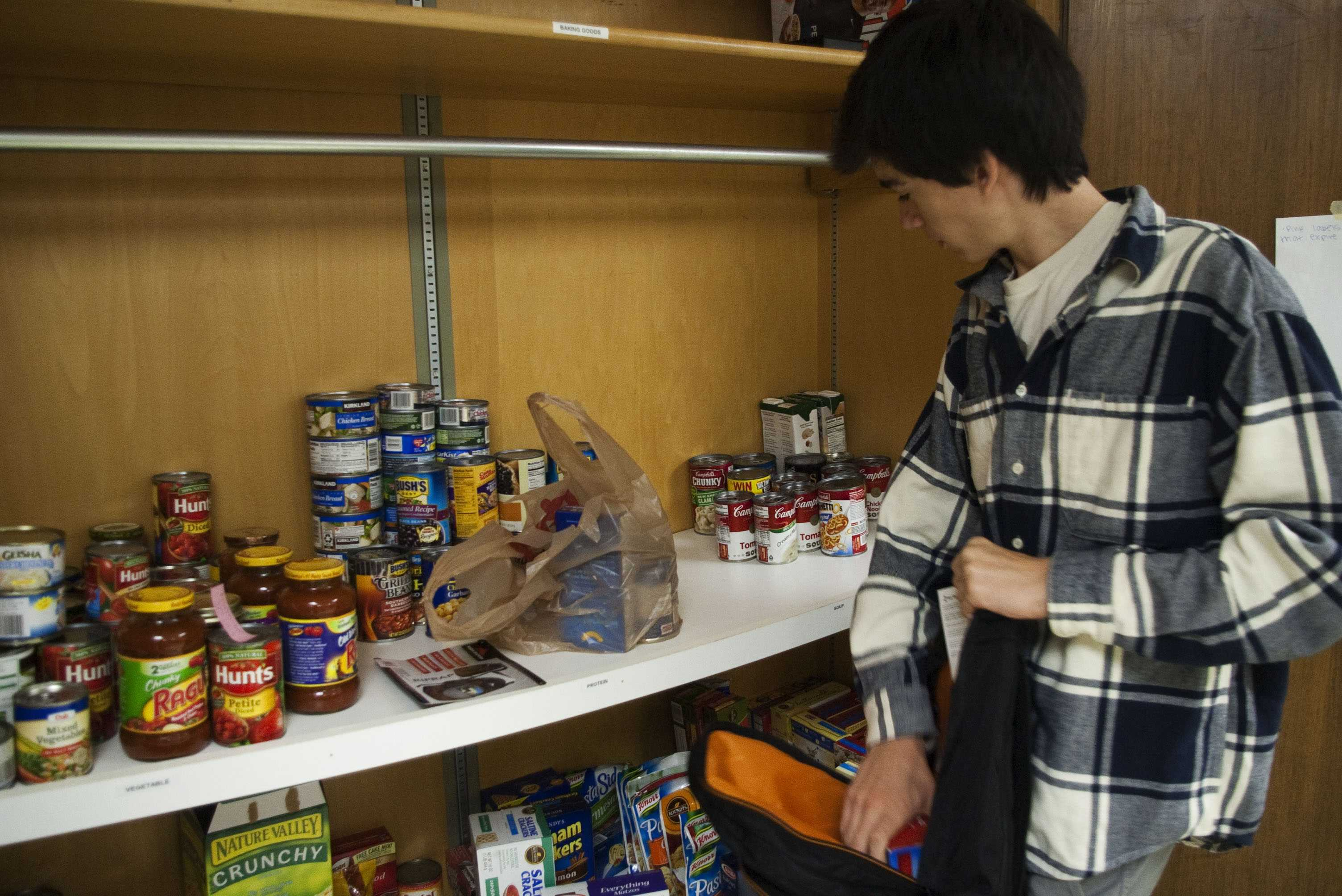 Finding Inspiration: Junior Conor Hannon organizes food for the 'bird feeder' program at the high school for students in need. The food will be put into backpacks and sent home with students over the weekend.