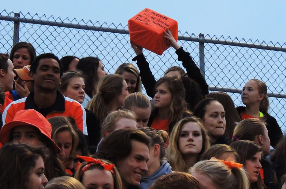 Fans pass around a donation box  at the April 11 girls lacrosse game to raise money for McManus family.