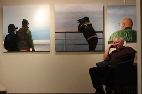 Contemporary artist Jerry Majkrzak sits among three of his paintings during a small preview of his work May 7. He is preparing for upcoming Art-A-Whirl festival May 15-17.