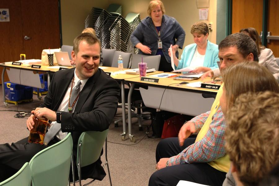 Interim principal talks with other school staffers before the school board meeting May 11.