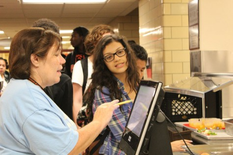 Cristi Beightol works at the checkout line during lunch Sept. 17. along with all the other nutritional services staff, Beightol said she enjoys the daily interaction with students in the cafeteria.