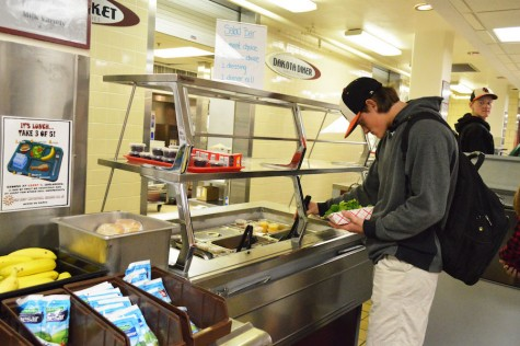 Sophomore Riley Dvorak creates a salad at the salad bar in the lunch line.