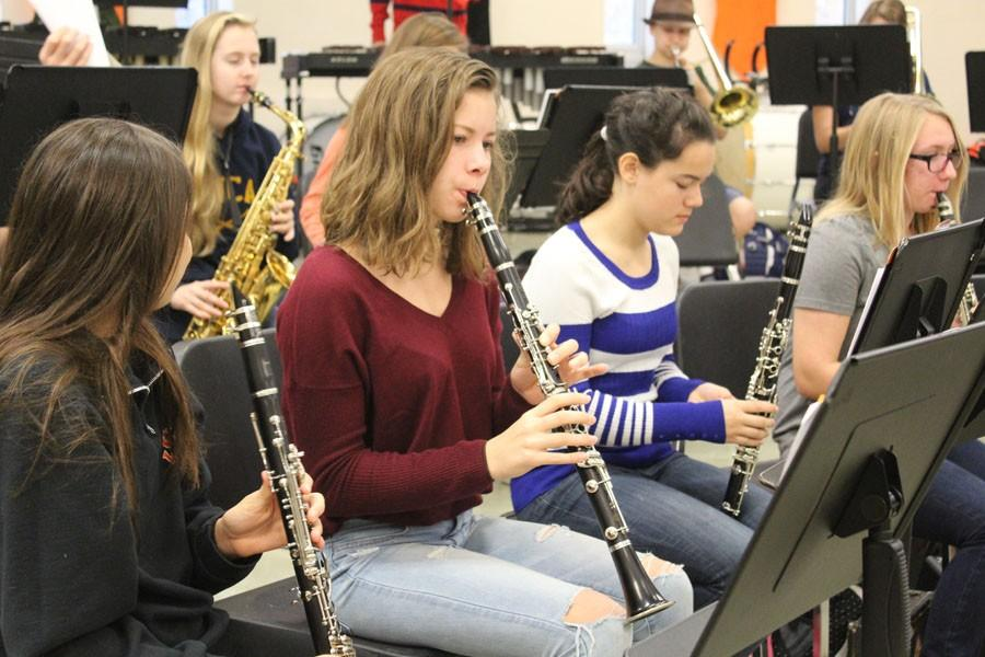 Freshman+Lexi+Lee+looks+over+her+music+while+band+conductor+Steve+Schmitz+prepares+for+mass+rehearsal.++