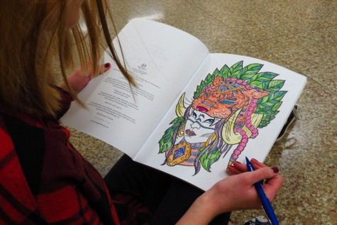 Junior Megan Wojtasiak adds the finishing touches to her artwork in her coloring book.