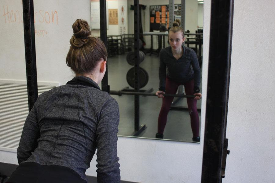 Muscle gains: Senior Clara Slade performs a bent-over row while she works out Feb. 25 in preparation for her first bikini competition. Slade's next competition, called The NPC Gopher State Classic, is April 2 at the Minneapolis Convention Center.