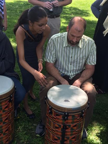 World drumming student senior Malena Jeffrey teaches a Cargill employee drum skills at the May 24 performance. Band teacher Steve Schmitz said he set up the event to provide students with additional musical opportunities following the cancellation of the Multicultural show.