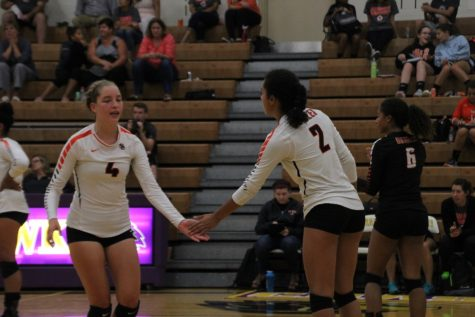 Junior captains Kim Lindgren (left) and Ella Trotter high-five during their game against Chaska.