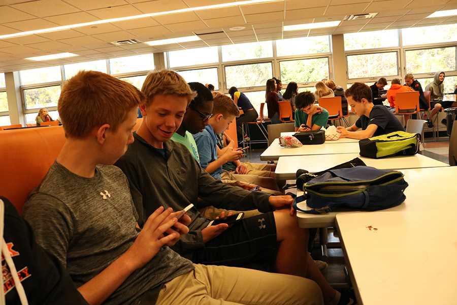 Freshmen Jamie Sorenson, Jackson Aune, Bryan Okere and Ashton Williams use their cell phones during lunch. All four students are frustrated that they are not able to access some social media sites on the school Wi-Fi.