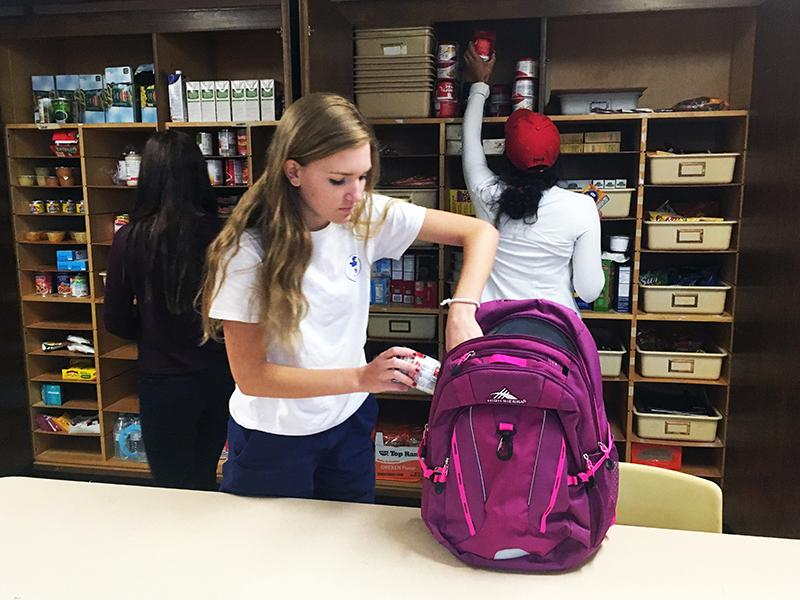 Junior Rosie Colacino packs a Birdfeeder backpack. Non-perishable food donations can be dropped off in B226.