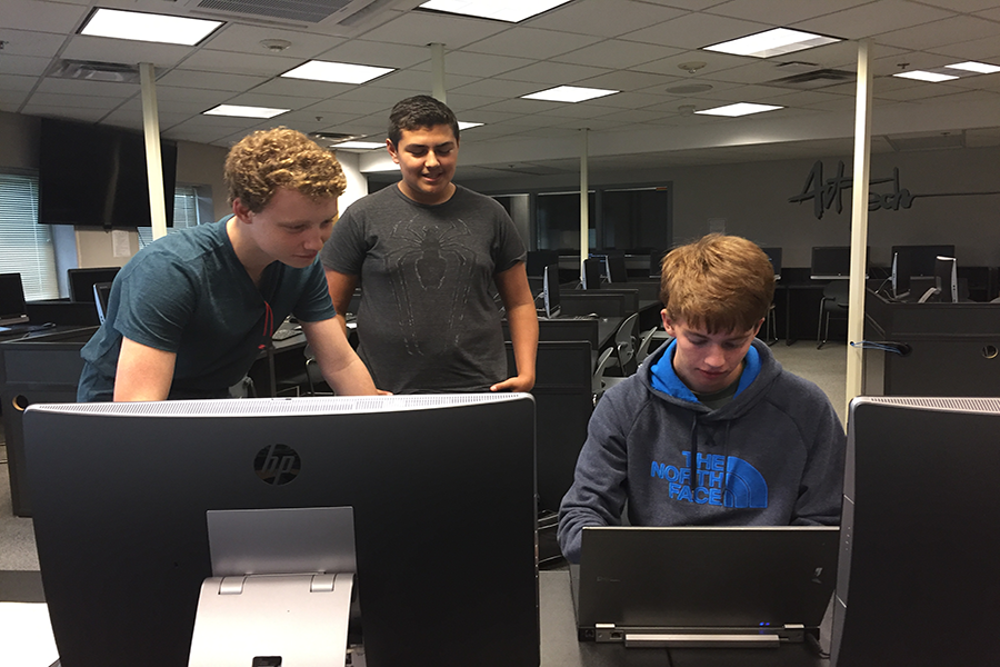 Junior Ryan Favour shows new members how to work the programming the system at the meeting on Oct. 4