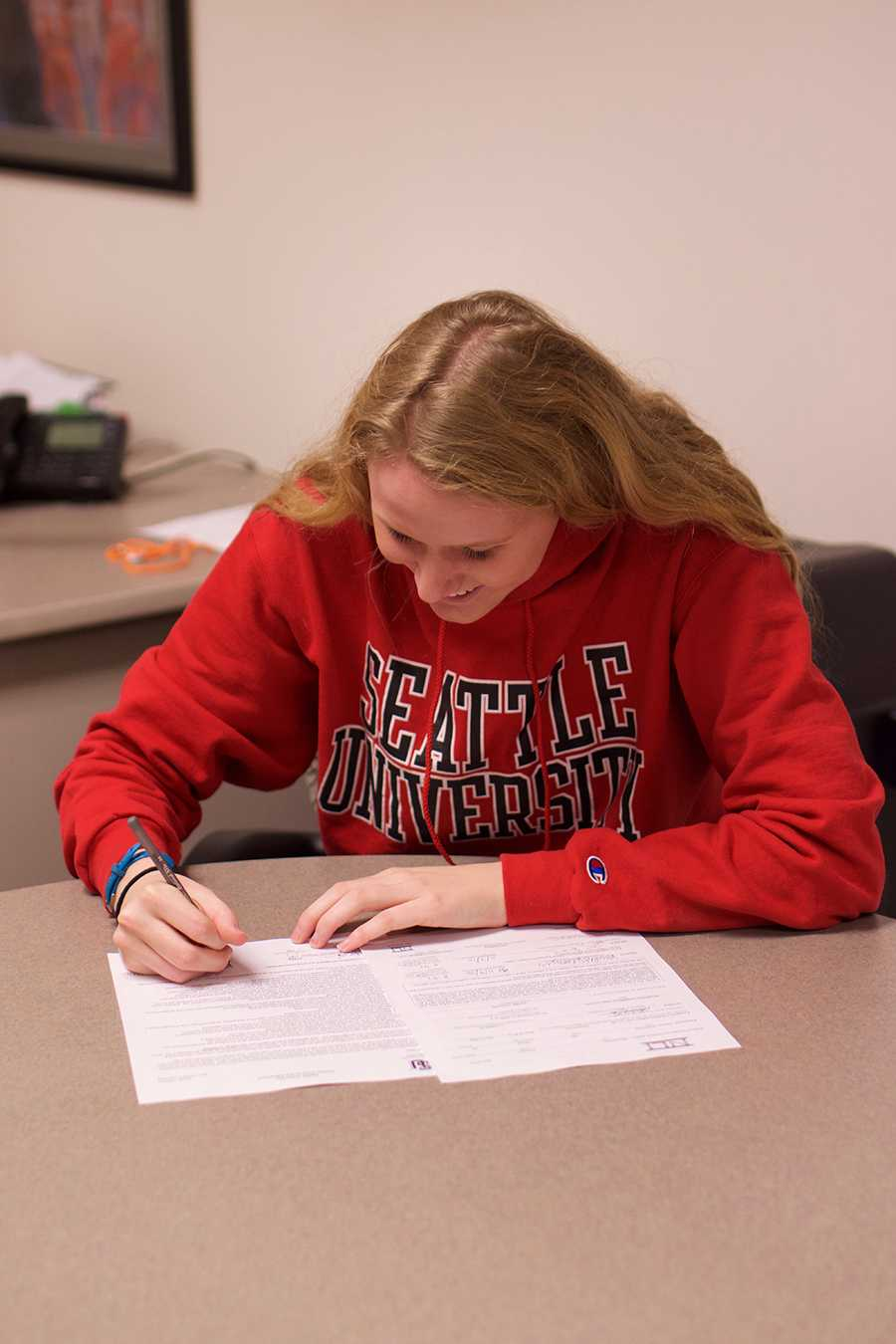Senior Kailey DeLozier signs her commitment to Seattle University for Division 1 swimming. She signed the contract Nov. 9.