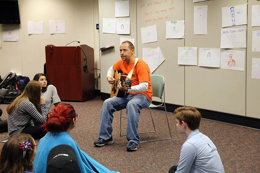Natural Helpers adviser Andrew Carlson plays the guitar as part of the group's all-day training Oct. 28. Club members are now available to meet with students for peer counseling.