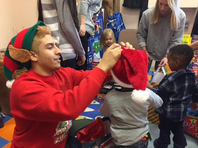 Senior Ernesto Garcia puts a hat on a preschoolers head during DECAs visit at the Family Partnership Dec. 20. DECA brought gifts for all the preschoolers who are in need and may not get any gifts during the holiday season.