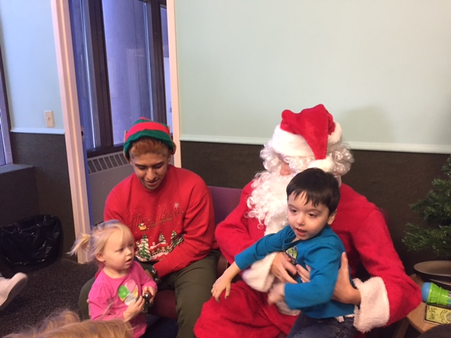Seniors Ernesto Garcia (left) and Ian Juaire (right) hold preschoolers on their laps during their visit to the Family Partnership preschool. DECA visited Dec. 20.
