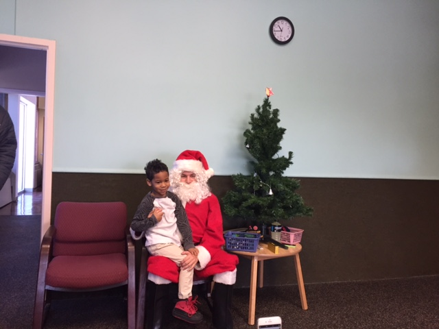 Senior Ian Juaire dresses up as Santa Claus and holds a preschooler on his lap. DECA attended the Family Partnership preschool Dec. 20.