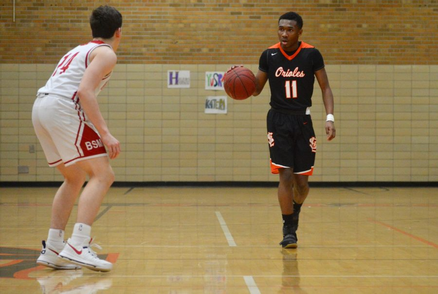 Junior guard Cire Mayfield dribbles the ball up the court during the first half of Park's Feb. 24 home game against Benilde. The Orioles defeated the Benilde-St. Margarets Red Knights 77-57 Feb. 24, which improved the Orioles' record to 12-12.