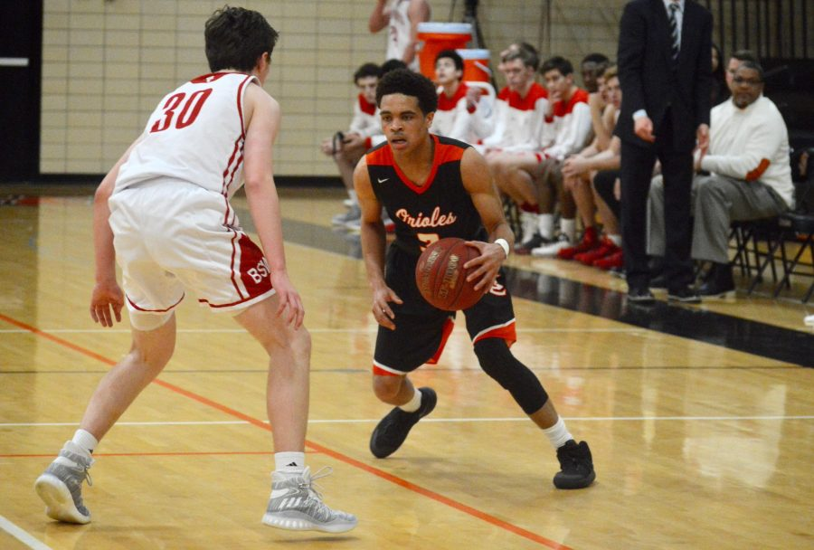 Senior guard Richard Green III prepares to drive past a Benilde defender late in the first half of the Orioles' victory over the Red Knights. The Orioles defeated the Benilde-St. Margarets Red Knights 77-57 Feb. 24, which improved the Orioles' record to 12-12.