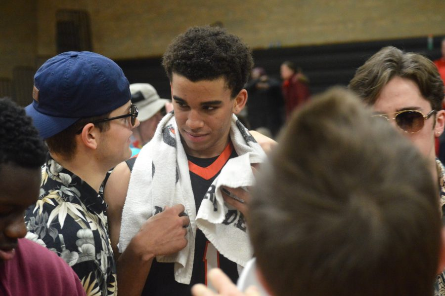 Seniors Mykal Howard (right) and Noah Fracassi (left) discuss the Orioles' Feb. 24 victory over Benilde on the court after the final buzzer. The Orioles defeated the Benilde-St. Margarets Red Knights 77-57 Feb. 24, which improved the Orioles' record to 12-12.