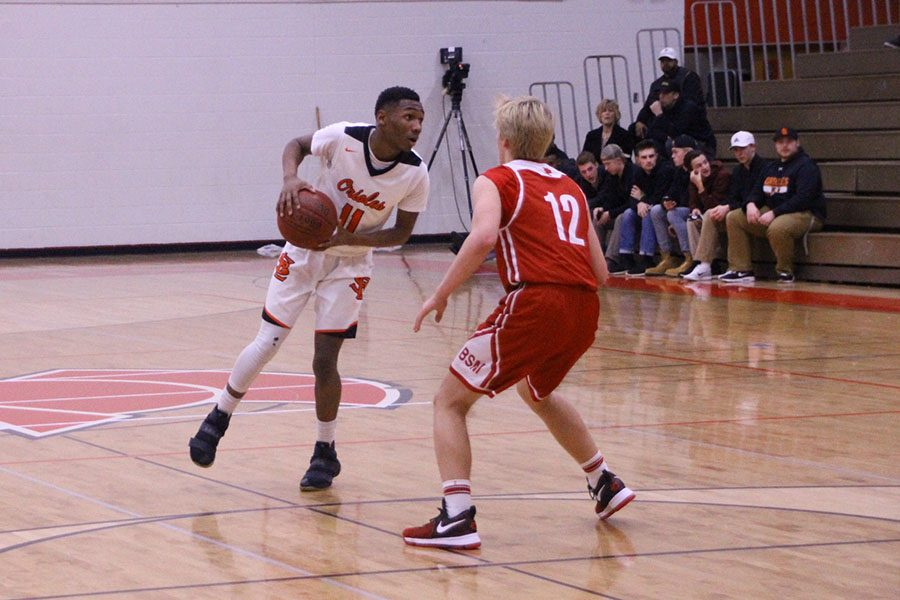Junior Cire Mayfield dribbles against a Benilde defender. The Orioles are currently in fifth place in their conference.