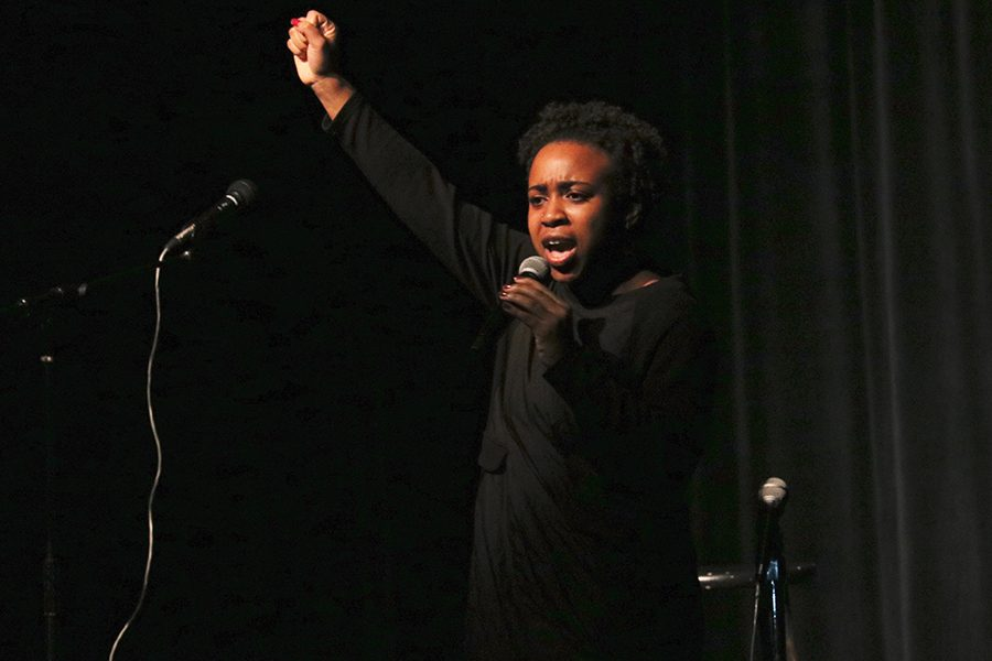 Senior Eben Managbe recites a poem by Maya Angelou at the Black History Month show. Managbe raised her fist at the end of the performance as an act of solidarity.