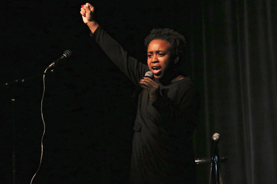 Senior+Eben+Managbe+recites+a+poem+by+Maya+Angelou+at+the+Black+History+Month+show.+Managbe+raised+her+fist+at+the+end+of+the+performance+as+an+act+of+solidarity.