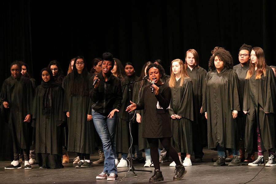 Seniors+Eben+Manegbe+and+Usera++Jara+perform+a+song+during+the+Black+History+Month+show+while+the+choir+sings+along+in+the+background.+Manegbe+also+performed+a+poem+along+with+the+song.+