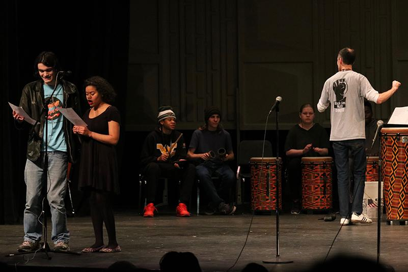 Seniors+Scott+Eaves+and+Makila+Jones+sing+Day+O+at+the+Black+History+Month+Show.+Band+director+Steven+Schmitz+leads+the+world+drumming+class+in+the+background+during+the+performance.