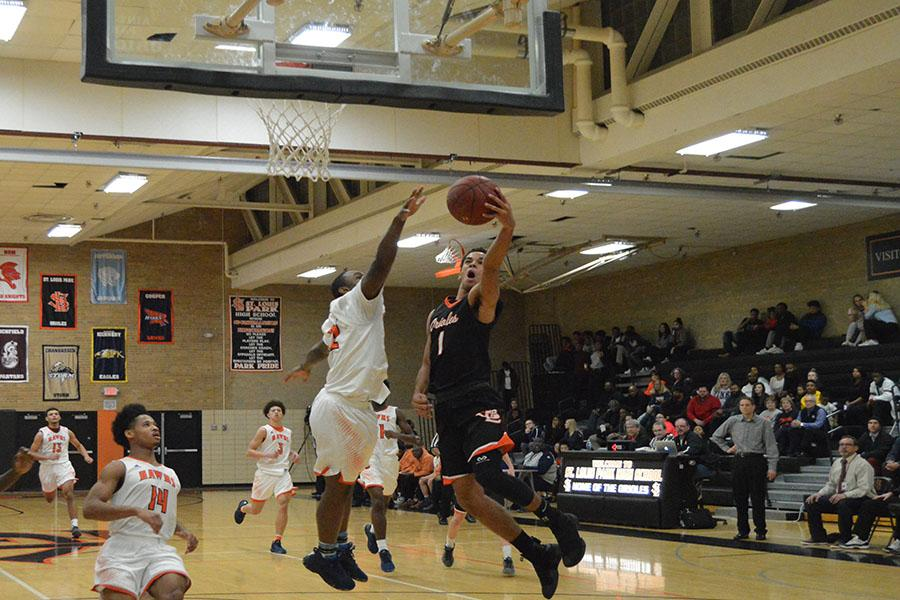 Senior Guard Mykal Howard goes for a layup against a Cooper defender at boys' basketball senior night Feb 28.  The team will play its first section game at 7p.m. March 3 against Chanhassen at Chanhassen High School.