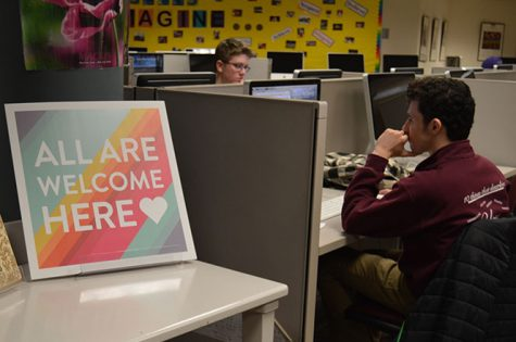 Senior Simon Lewin works on a computer  in the Library Media Center next to the All Are Welcome Here sign. Media Specialist Ellen George put the sign to send a message of acceptance and understanding.