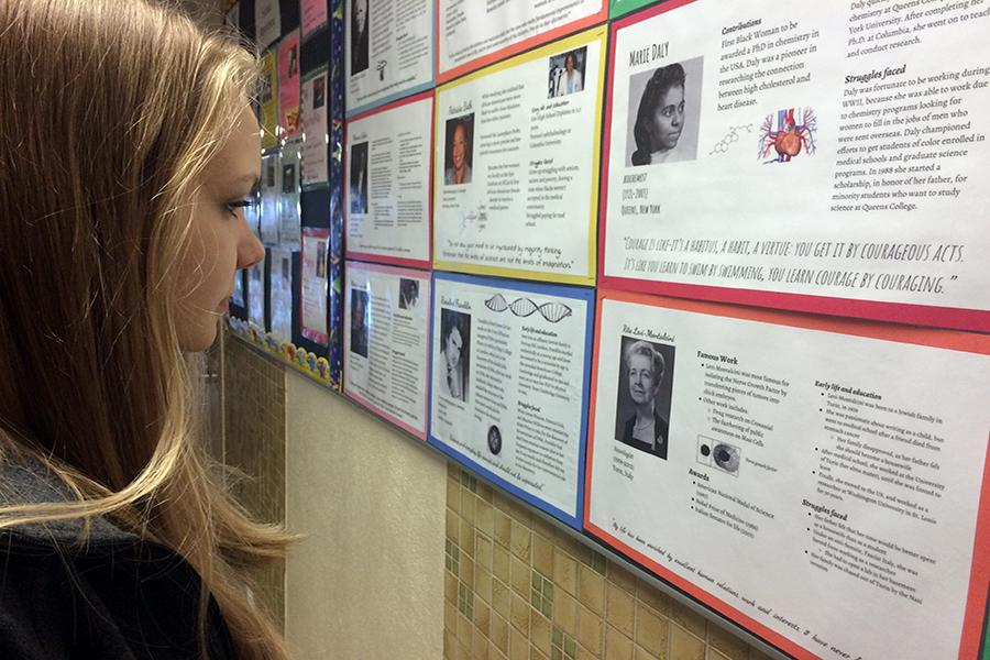 Junior Lindsey Prestholt views posters made by IB Biology seniors in the science hallway. IB Biology teacher Julie Schilz hoped the research her students did on notable women in science would educate and inspire others at Park.