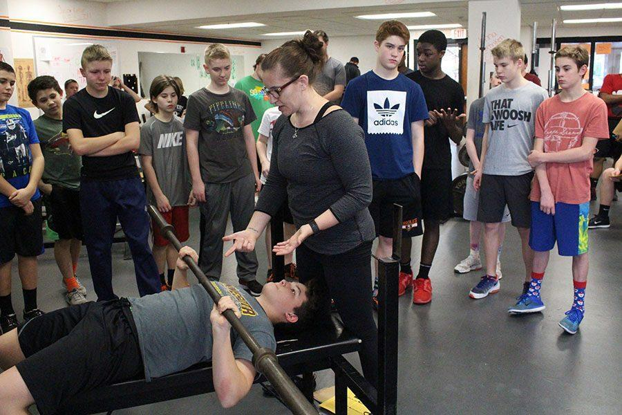 Strength+coach+Jessica+Gust+uses+freshman+Sam+Thyne+to+demonstrate+how+to+spot+someone+while+bench+pressing+Feb.+27.+This+week+students+had+fitness+testing+to+track+their+progress.+