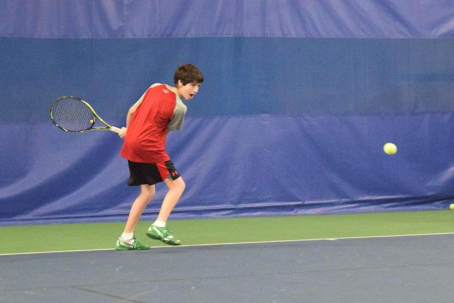 Freshman Rafe Covin prepares to swing at the ball during captains' practice March 17. According to head coach David Breitenbucher, the boys' tennis team will be able to continue having both a JV team and a varsity team this year despite low numbers.