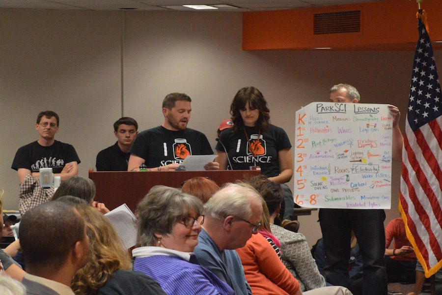 (From left) At the April 24 School Board meeting, Science teachers Patrick Hartmann and Kristen Moravetz speak out against the decision to cut the ParkSci program from the 2017-2018 budget, while science department chairman Mark Miller holds a sign detailing the benefits of the ParkSci program.