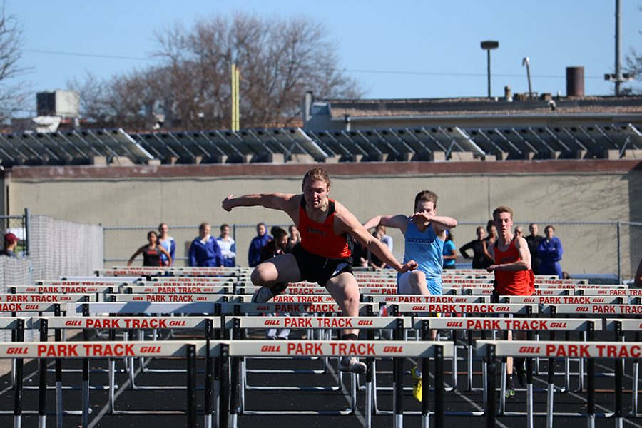 Senior captain Owen Geier jumps over hurdles during the 110 meter race. Geier finished first in a time of 16.76 seconds.