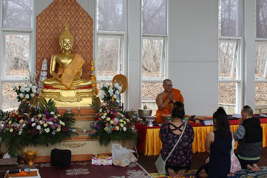 Wat Thai Buddhist temple hosted an open house on Sunday, April 9. In the shrine room, a buddhist monk prays with people who attended the open house.