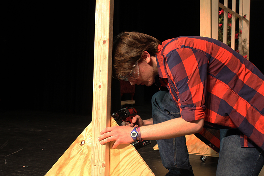 Cast and crew member, junior Thomas Bryant, works on building the set of the spring play, April 14.