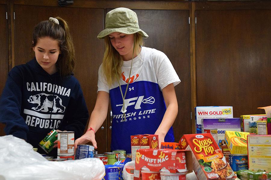Juniors Rosie Colacino and Annika Eldridge sort packaged foods.