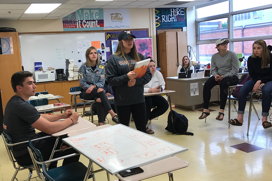 Echowan editors practice distributing yearbooks during class on May 19. Yearbook distribution will take place in the auditorium foyer May 22 and May 23.
