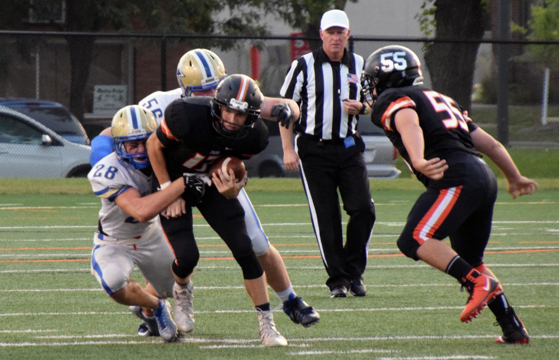 Senior varsity quarterback Jonny Sorenson attempts to break a tackle by Holy Angels' defense, Sept. 15.