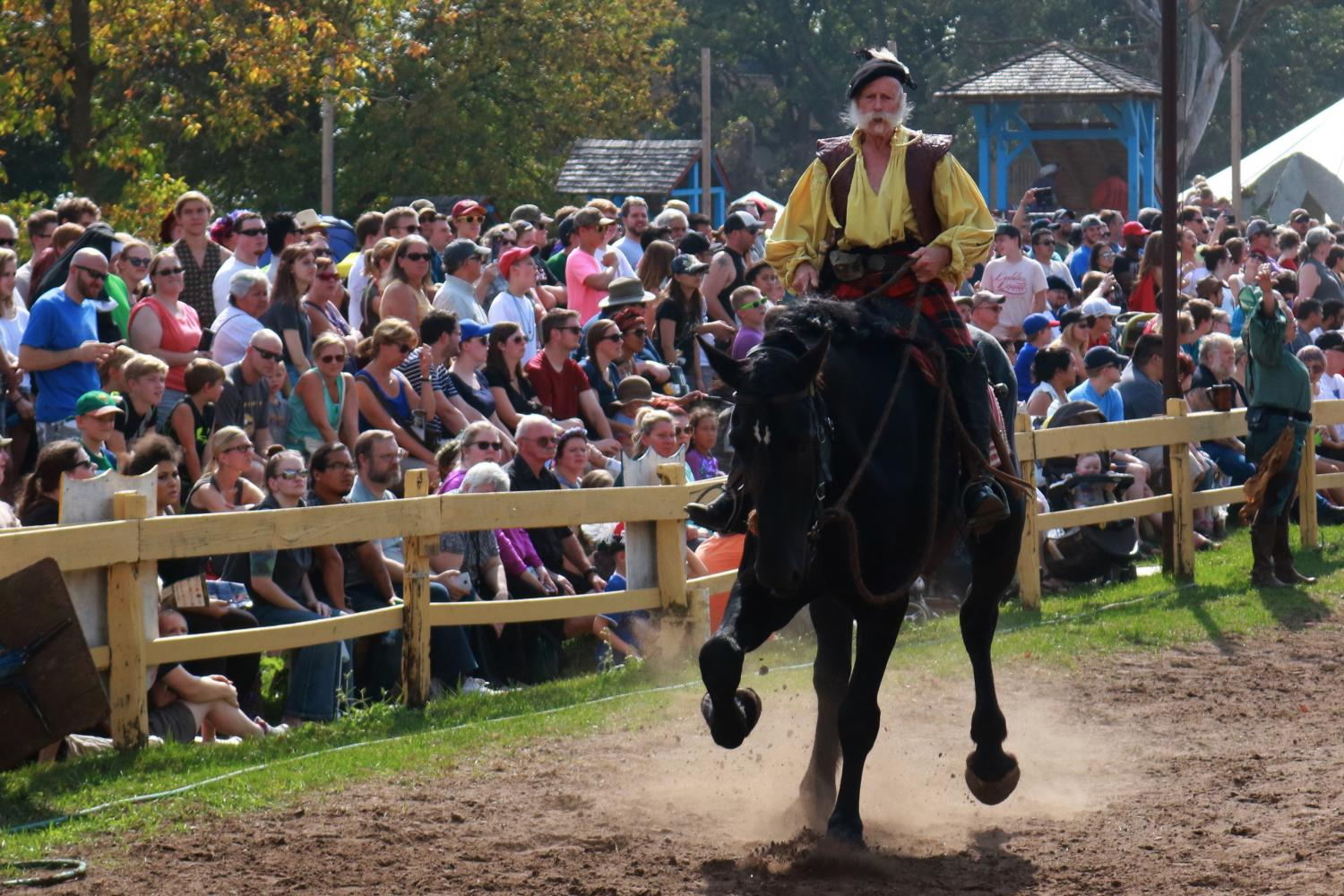 A knight marshal gallops across the jousting arena at the Renaissance Festival.