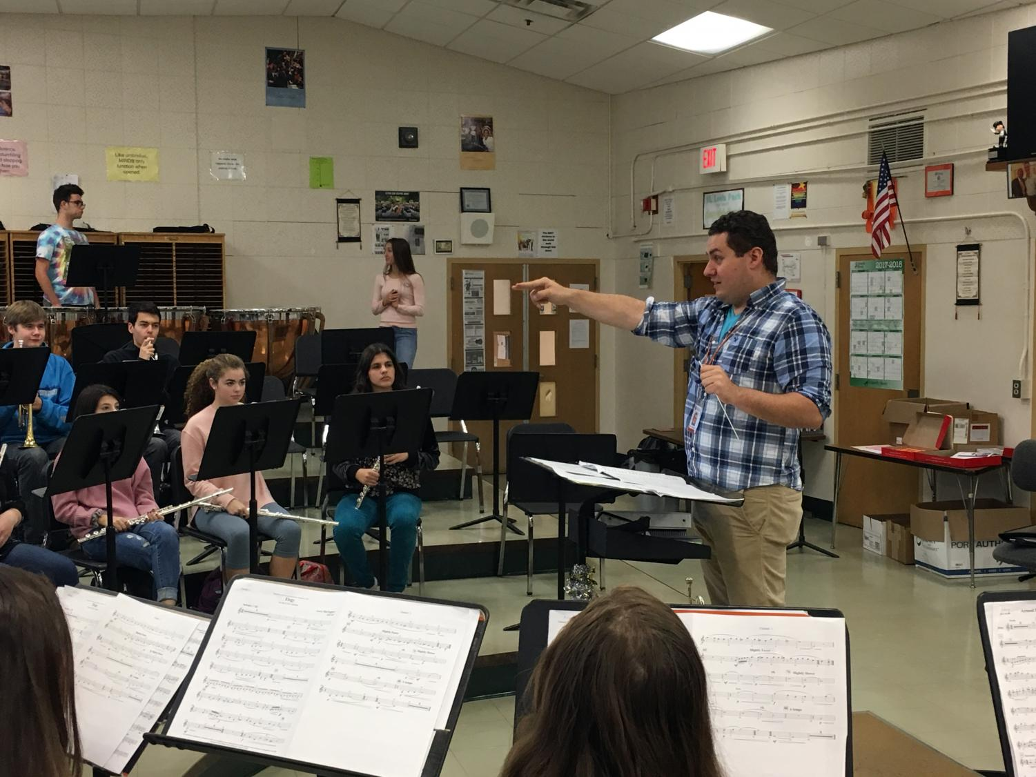 Band student teacher Sam Khwice conducts a performance during third hour band class Oct. 25.