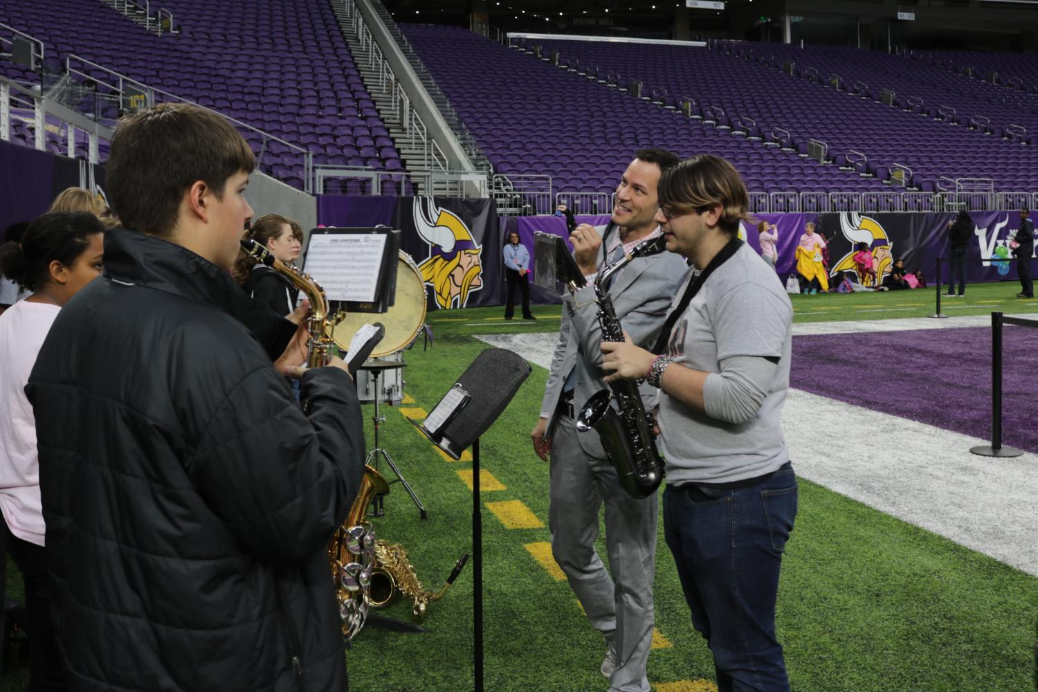 Senior Ethan Rickert stands alongside band teacher Steven Schmidtz during one of their warmups at the Making Strides Against Breast Cancer walk. The walk took place Oct. 8. at the U.S. Bank Stadium.