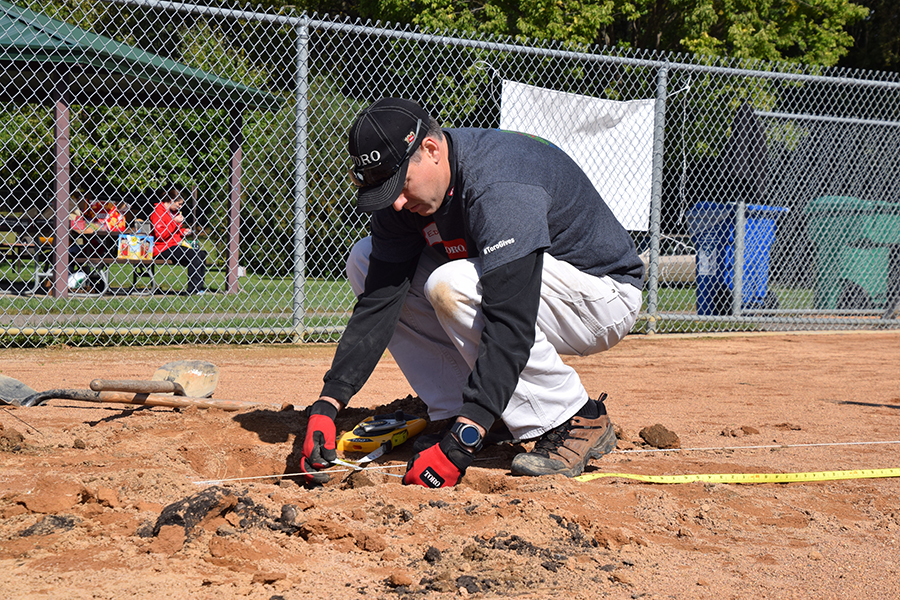 A TORO Volunteer measures the size of first base to shift the center of the base to align with the foul line, Oct. 4.