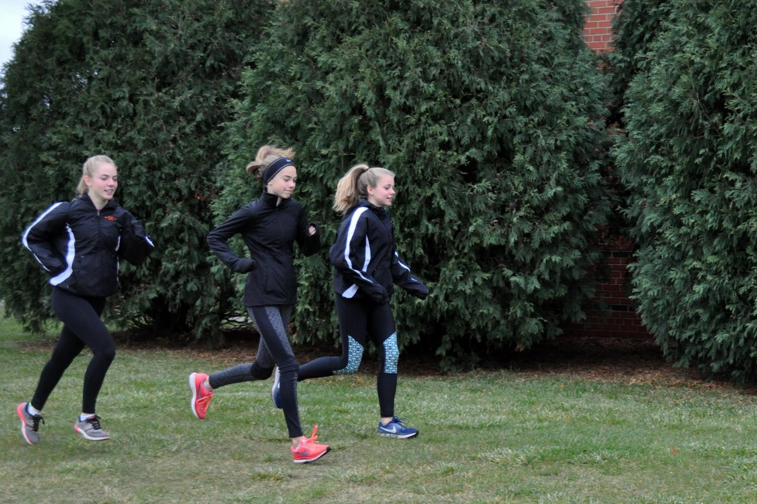 Sophomores Carissa Prestholdt and Kaia Myers run alongside fellow teammate eighth-grader Josie Mosby to help her train for the state meet Nov. 4.