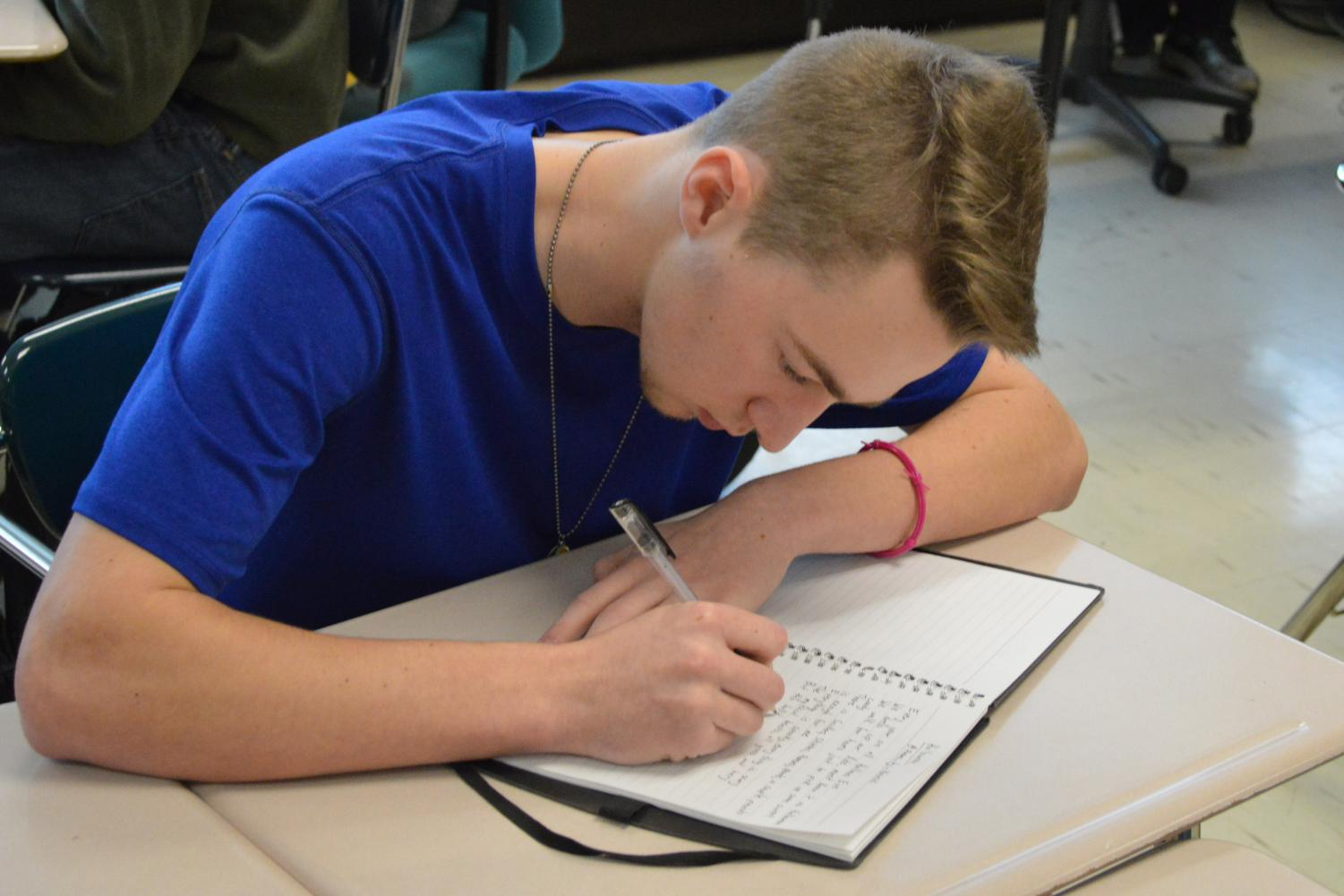 Junior Adam Kowski writes a poem during class on Monday, Nov. 6. He uploads his poems to his Instagram account dedicated to poetry. Follow him @poems_by_kowski on Instagram.