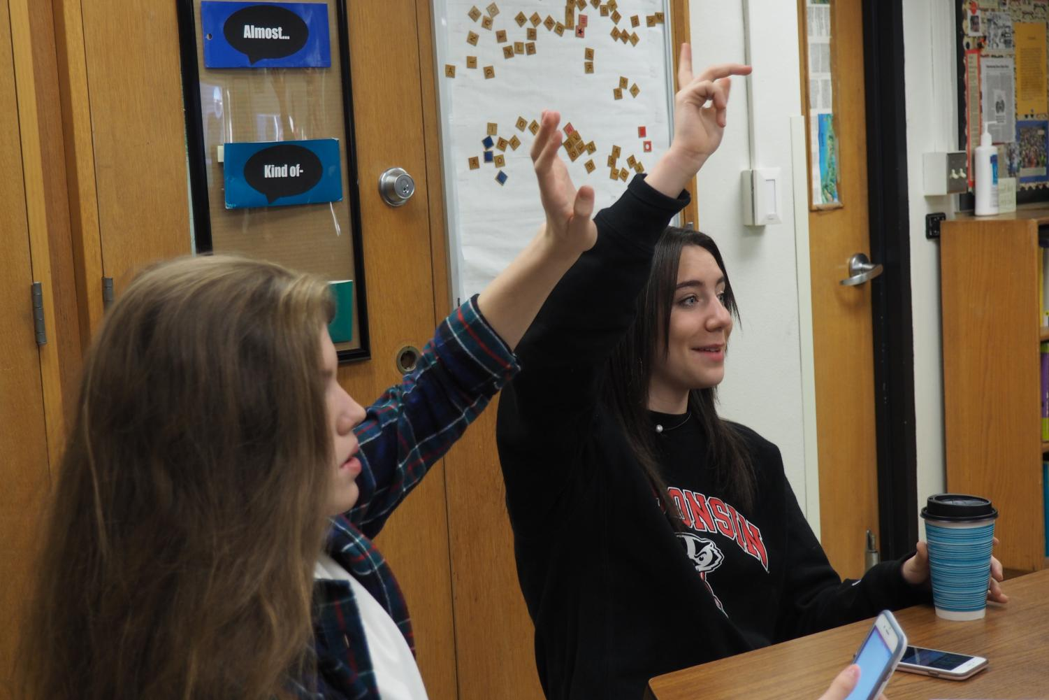 Student Council members Anna Wert and Hattie Kugler participate in a meeting Nov. 8 to prepare for upcoming pep fest in honor of the football team going to the State tournament.